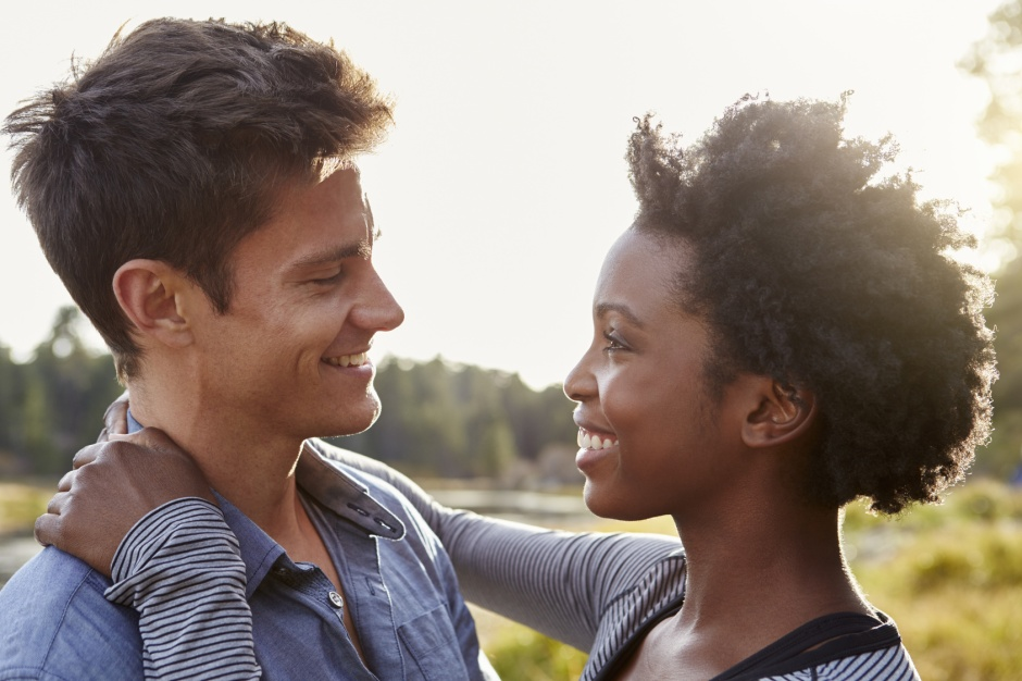Happy mixed race couple embracing in the countryside